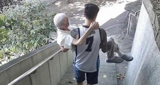 En Taiwán, joven lleva cargando a su abuelito para vacunarse